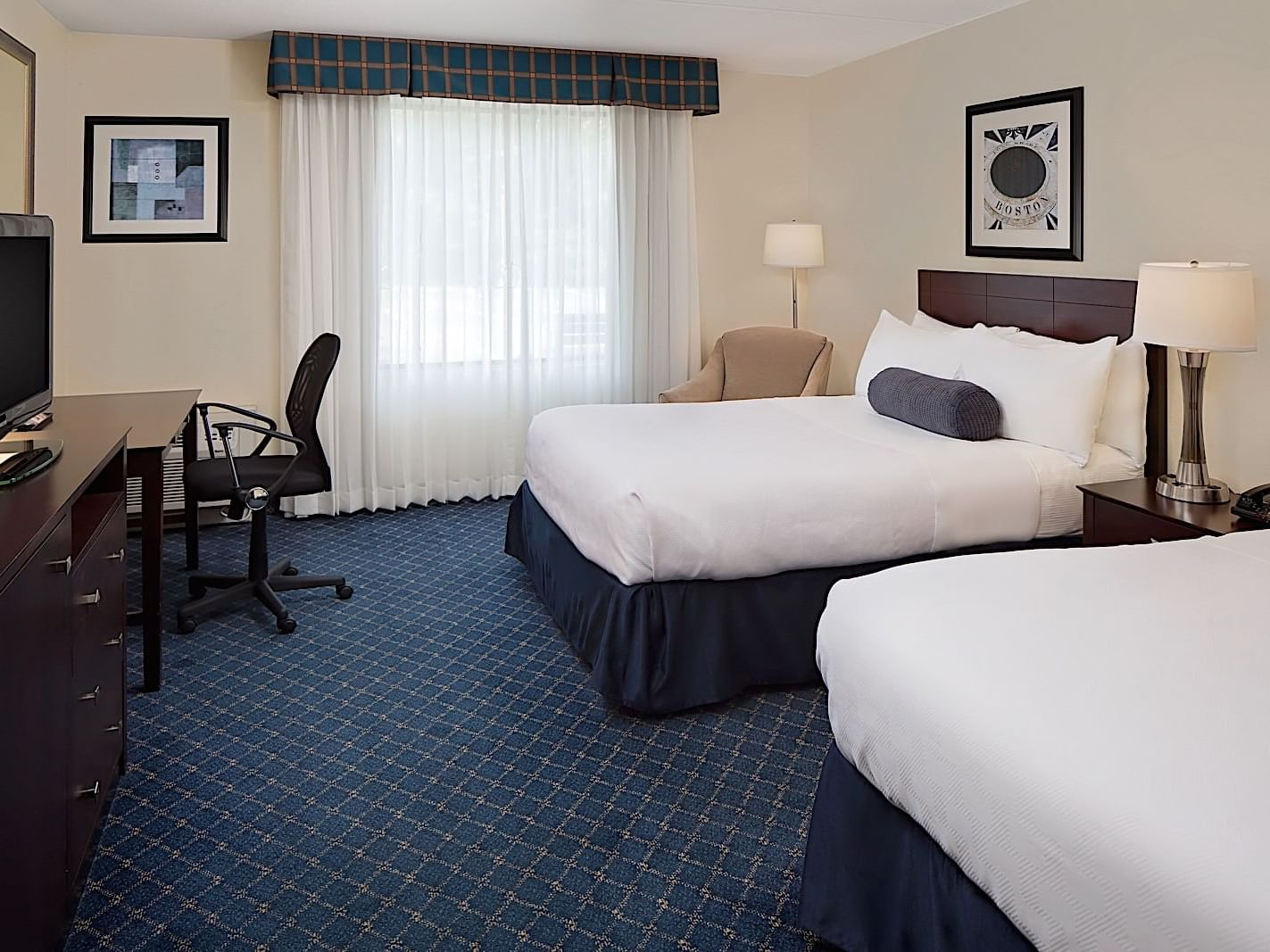 two beds in hotel room with blue carpet and window