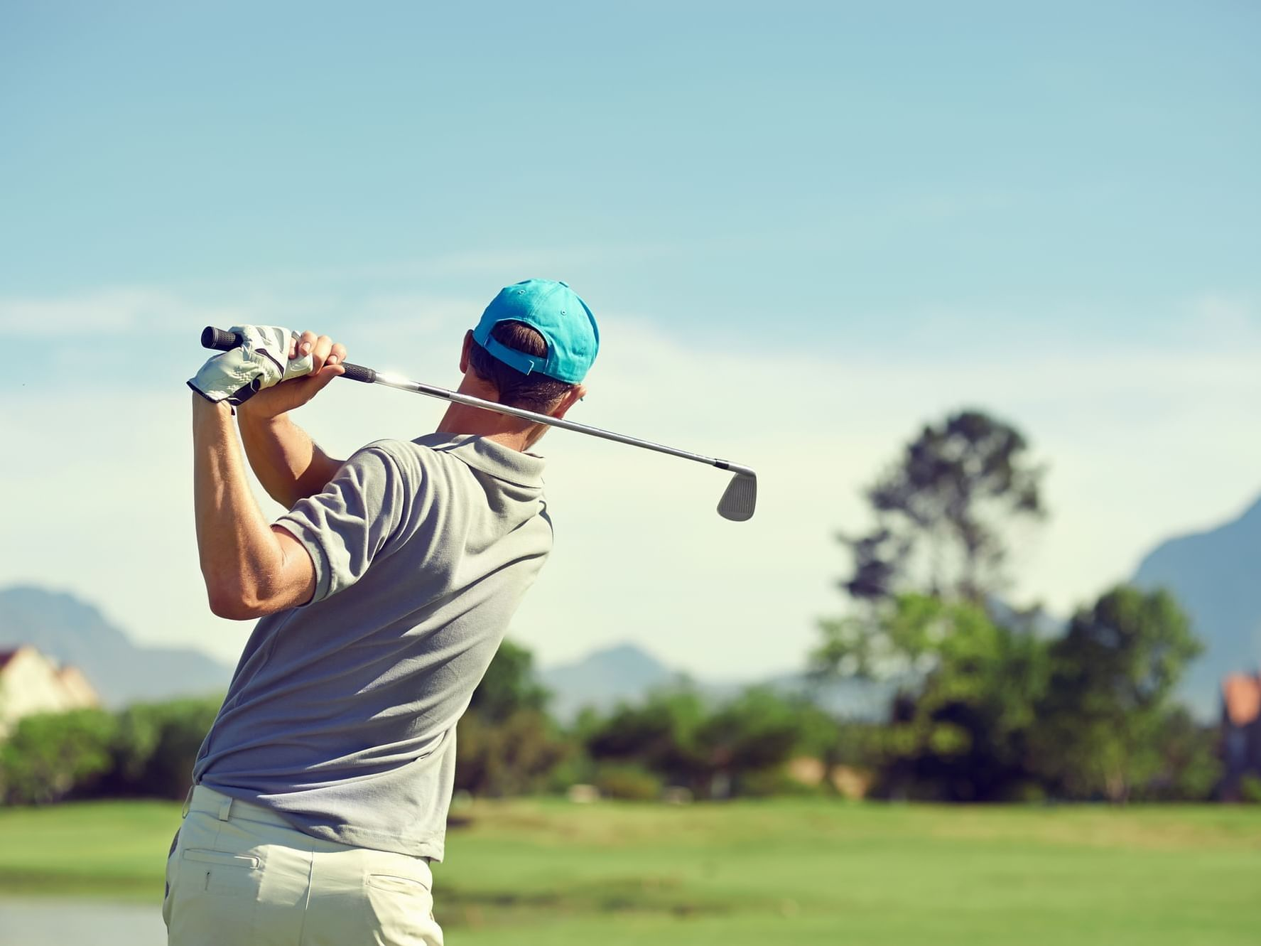 A golfer finishing his back swing after teeing off.