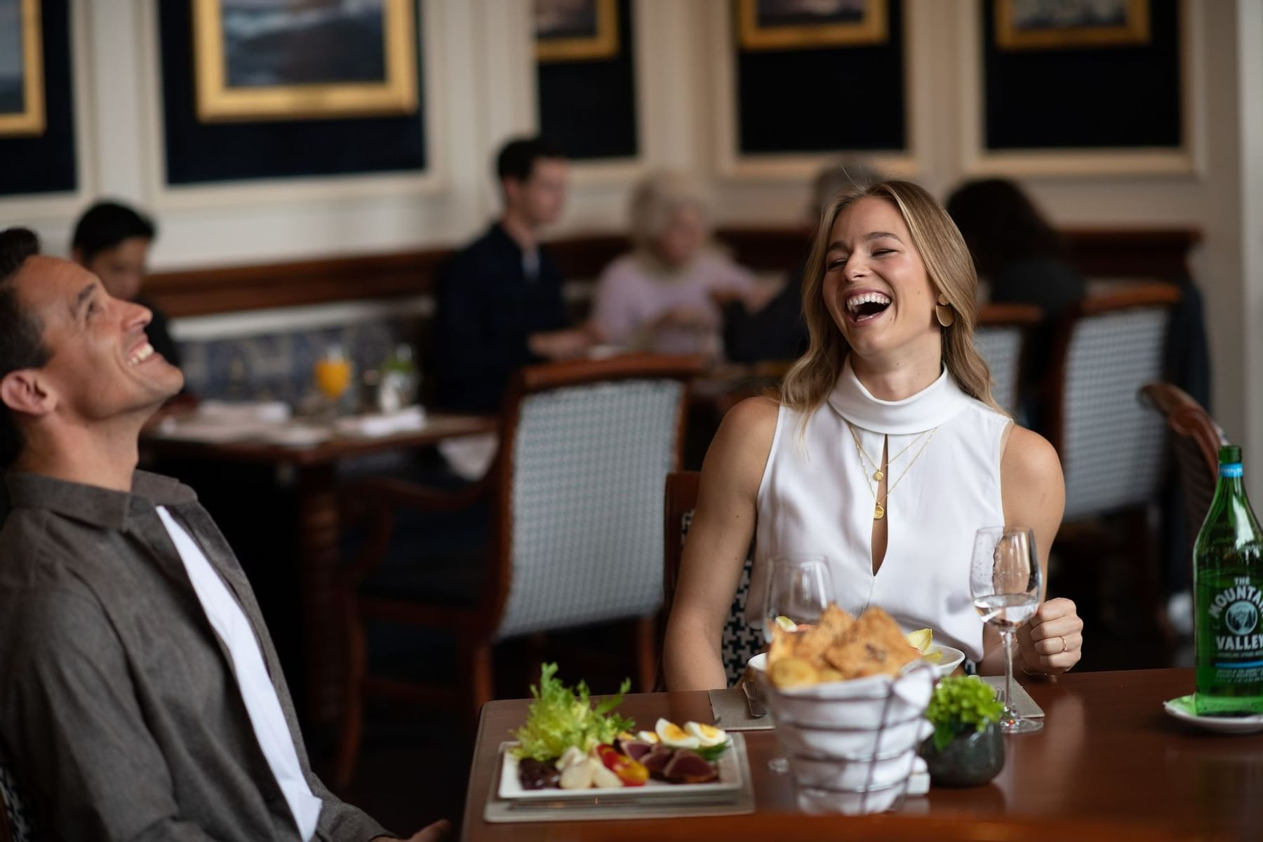 Two guests laughing at a dinner table