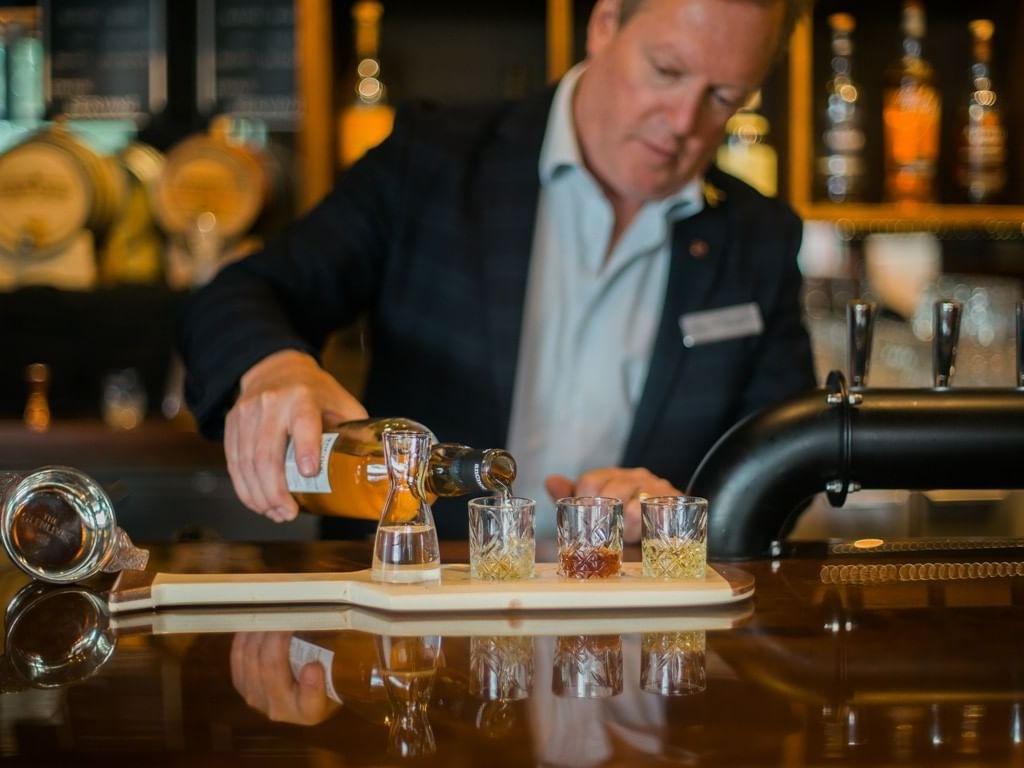A bartender pouring drinks at the Whiskey Room in Manteo Resort