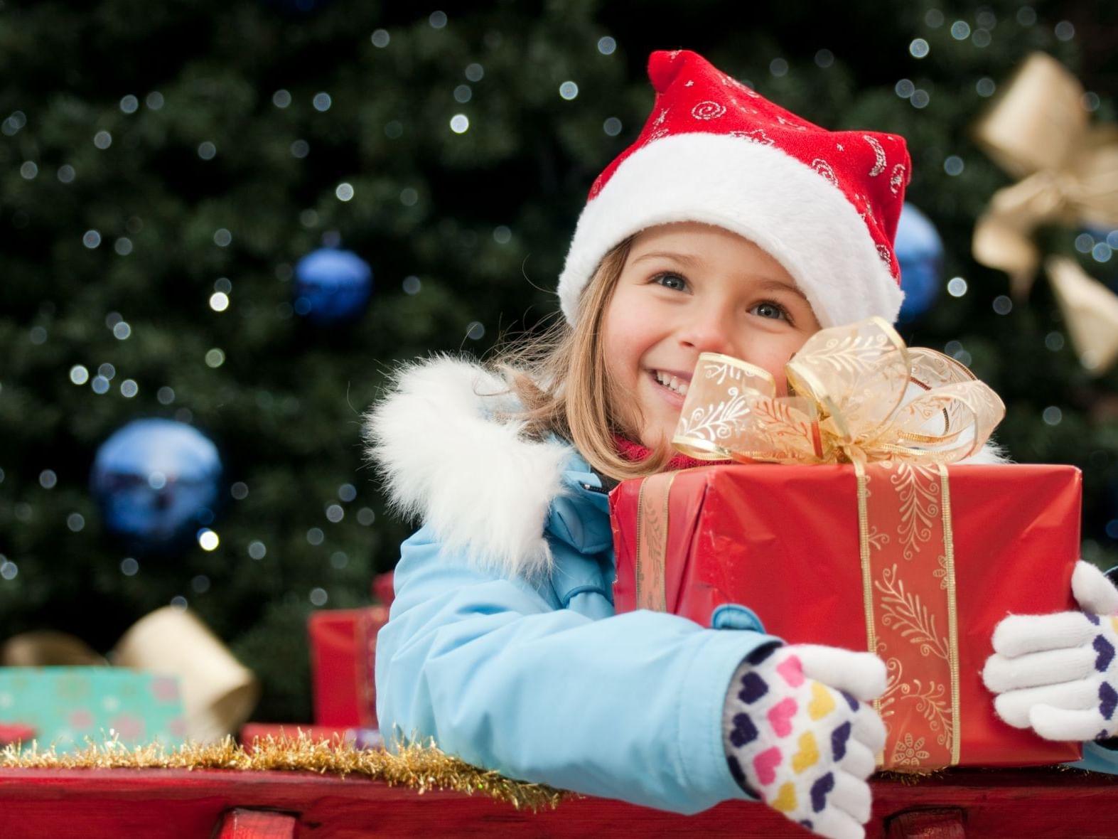 A girl hugging a Christmas present at Ana Hotels Sport Poiana