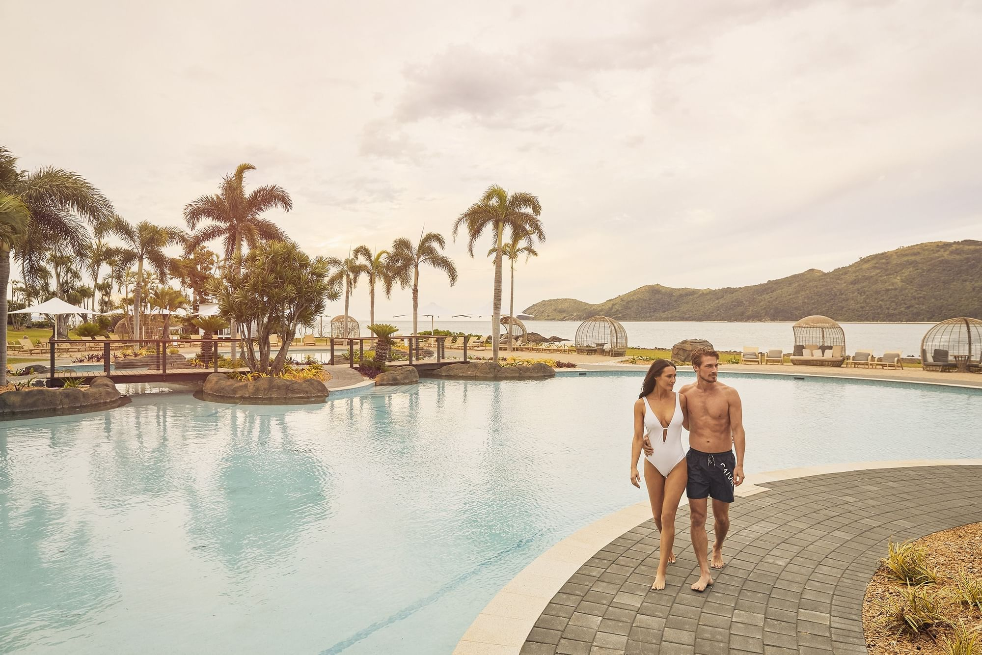 Couple spending time on pool deck at Daydream Island Resort