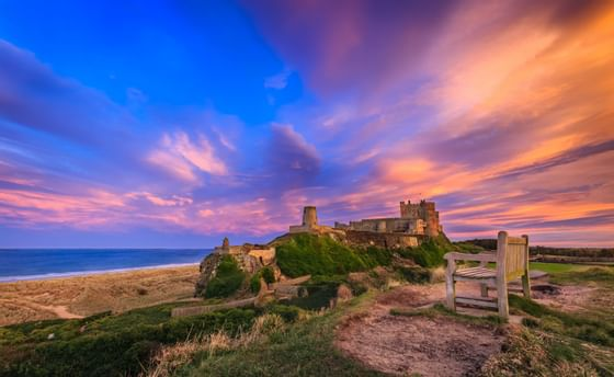 An ancient castle facing the sea during a sunset