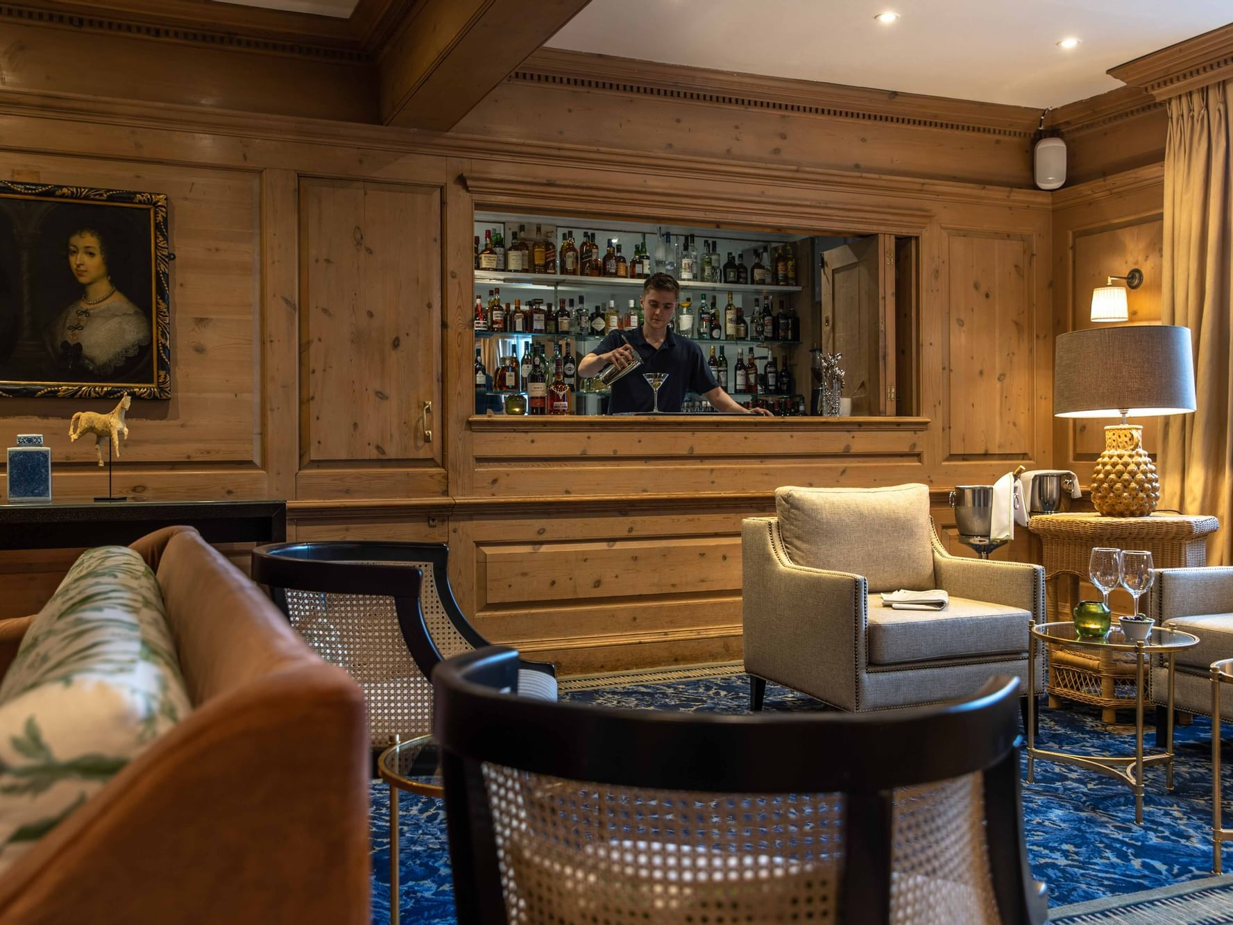 A bartender making drinks in The Clip Bar at The Relais Henley
