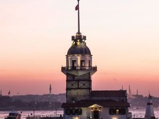 Exterior view of the Maiden's Tower with lights near CVK Hotels