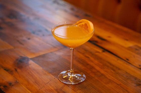 a cocktail with an orange slice