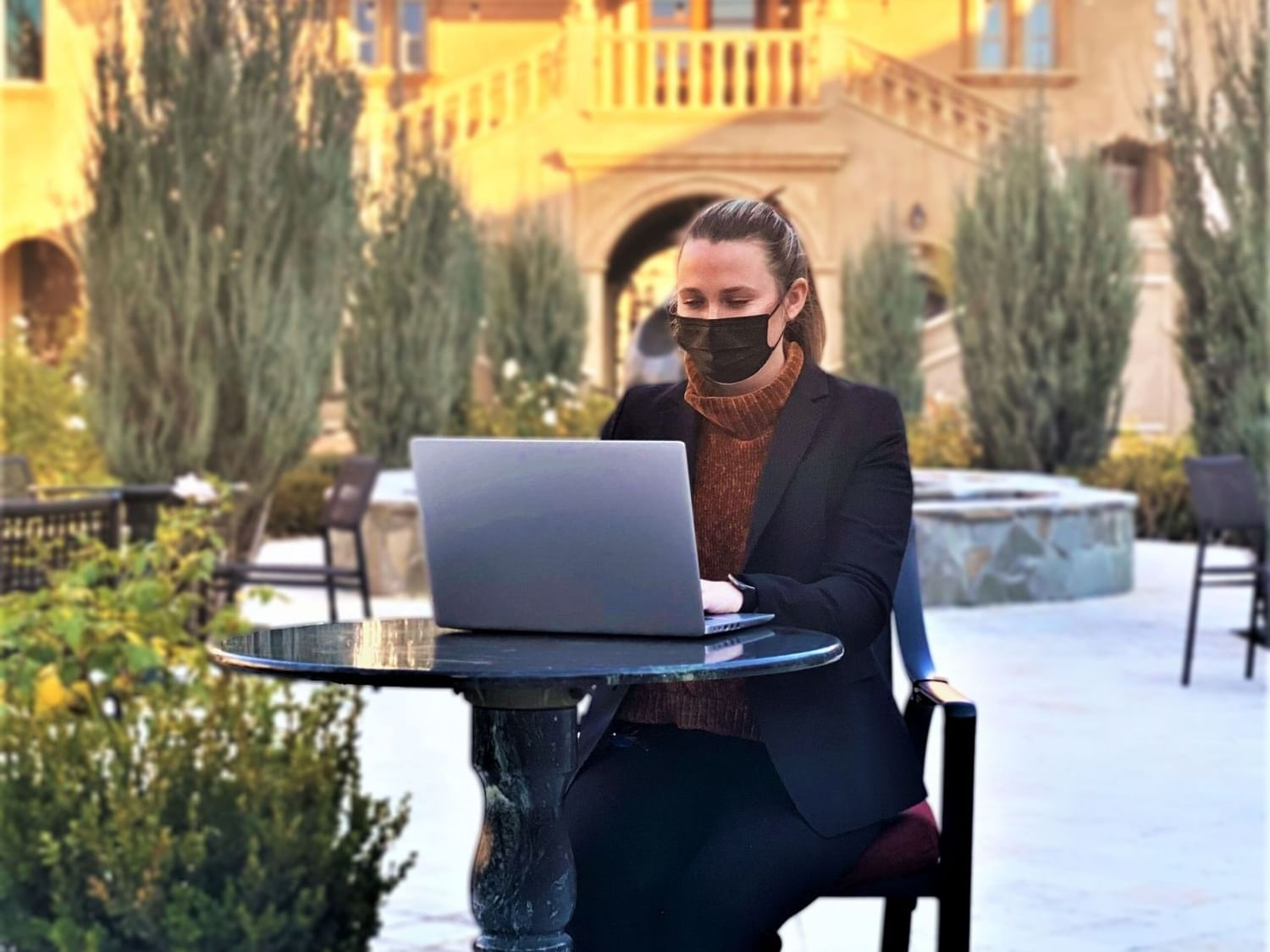 Woman with face mask sititng in terrace, working on laptop