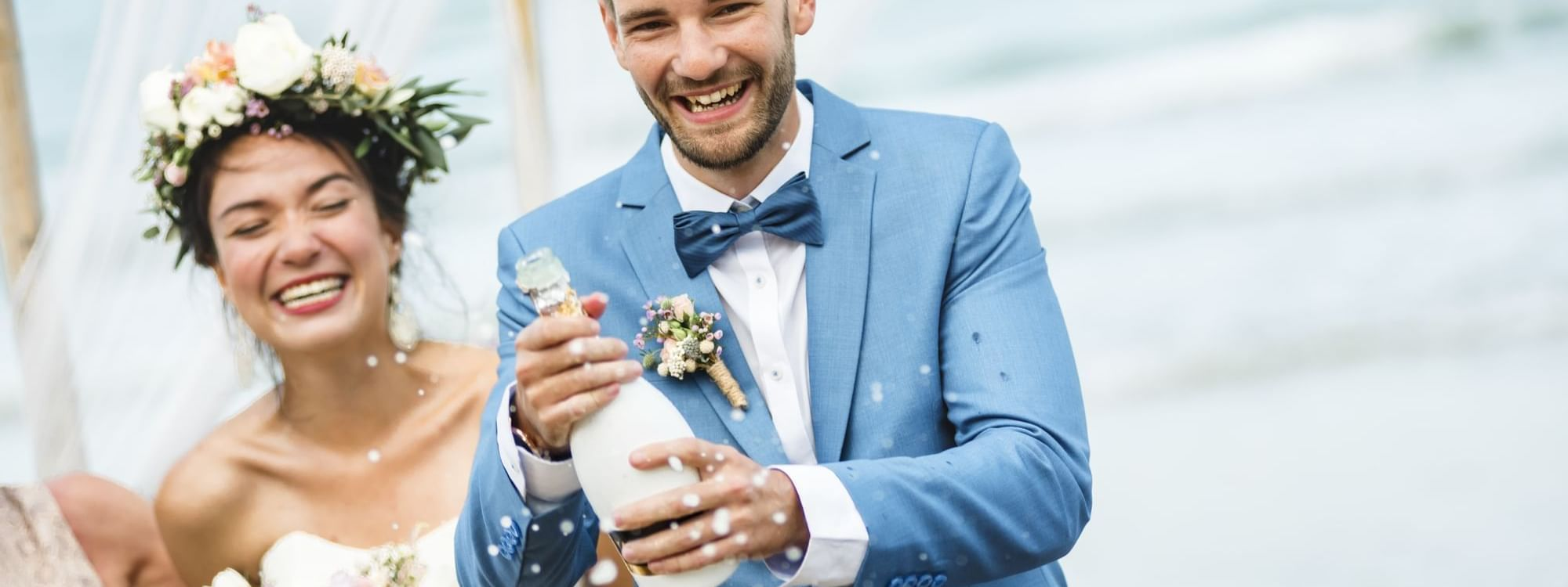 Groom shaking a champagne bottle at Daydream Island Resort