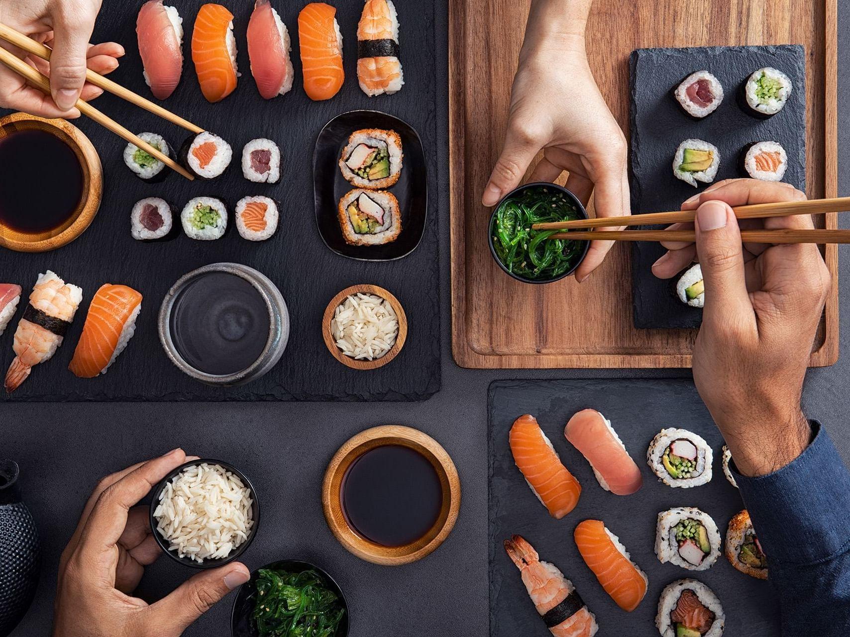 Man and woman sharing sushi with chopsticks at Henn Na Hotel