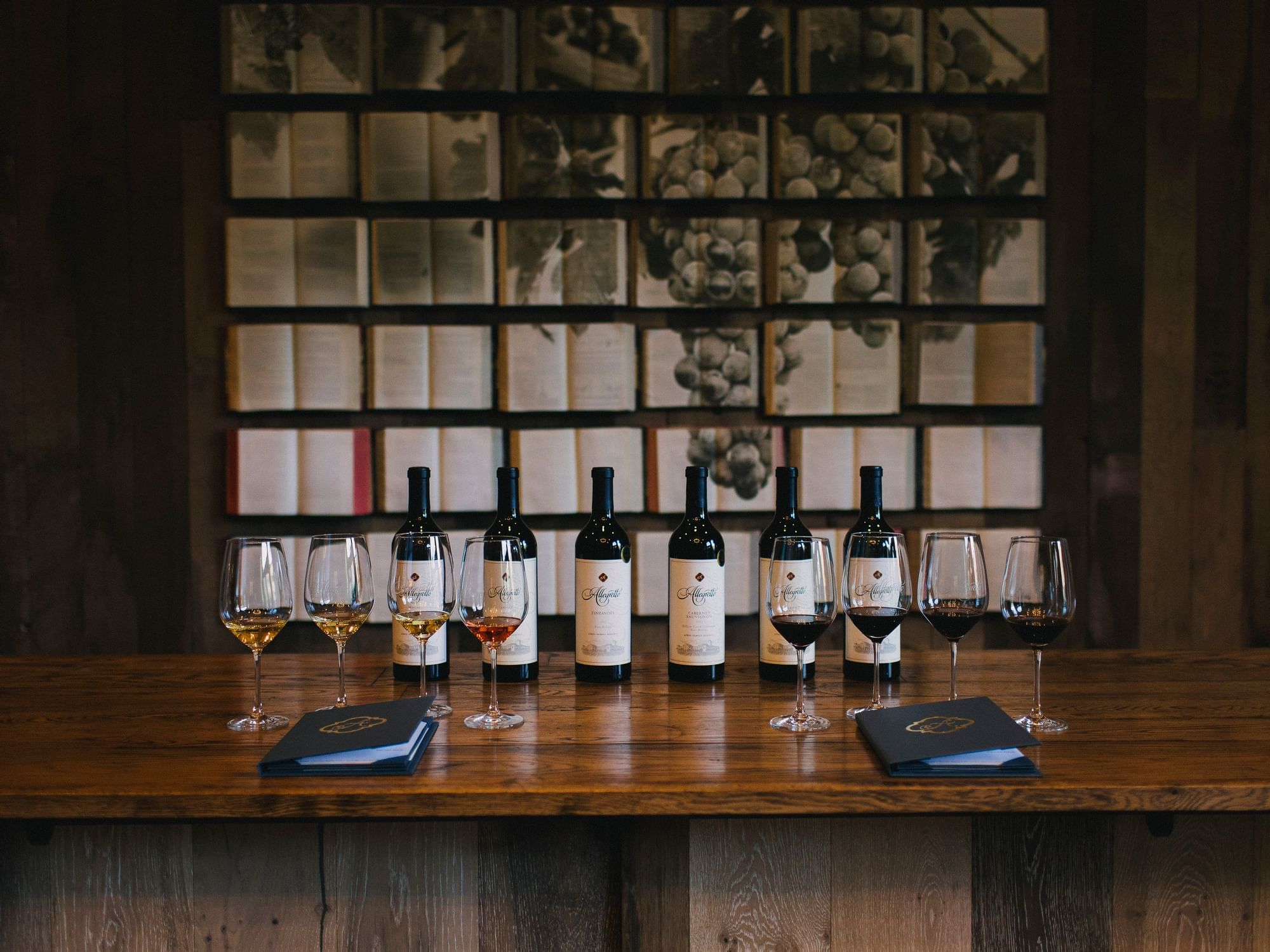 Allegretto's signature wine bottles lined up on a wooden table