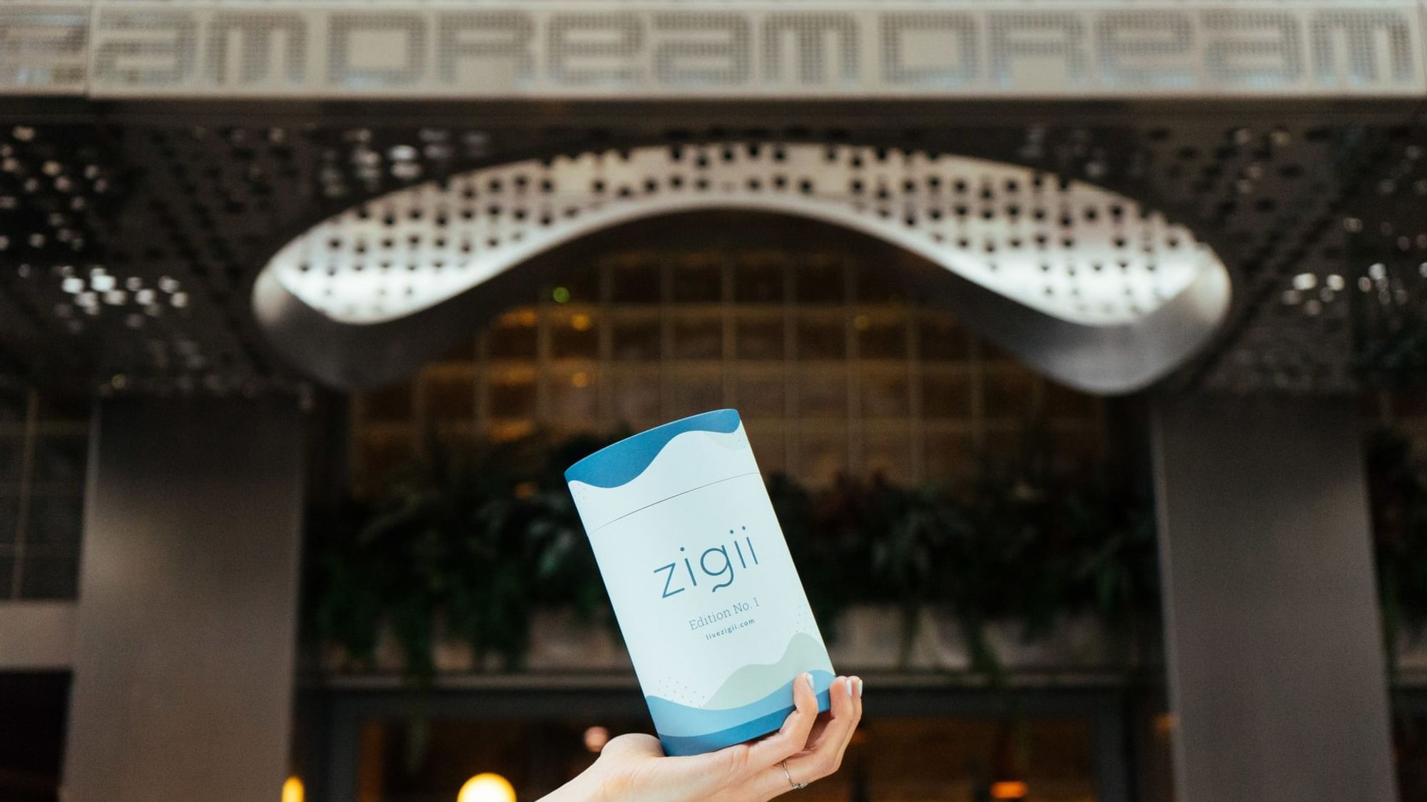 A bottle of 'zigii' on a women's hand with Dream Hotel view.