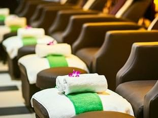 row of massage chair with fresh towels on leg rests