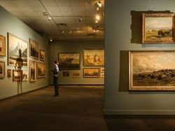 A man looking at the paintings in The Glenbow Museum near Carriage House Hotel
