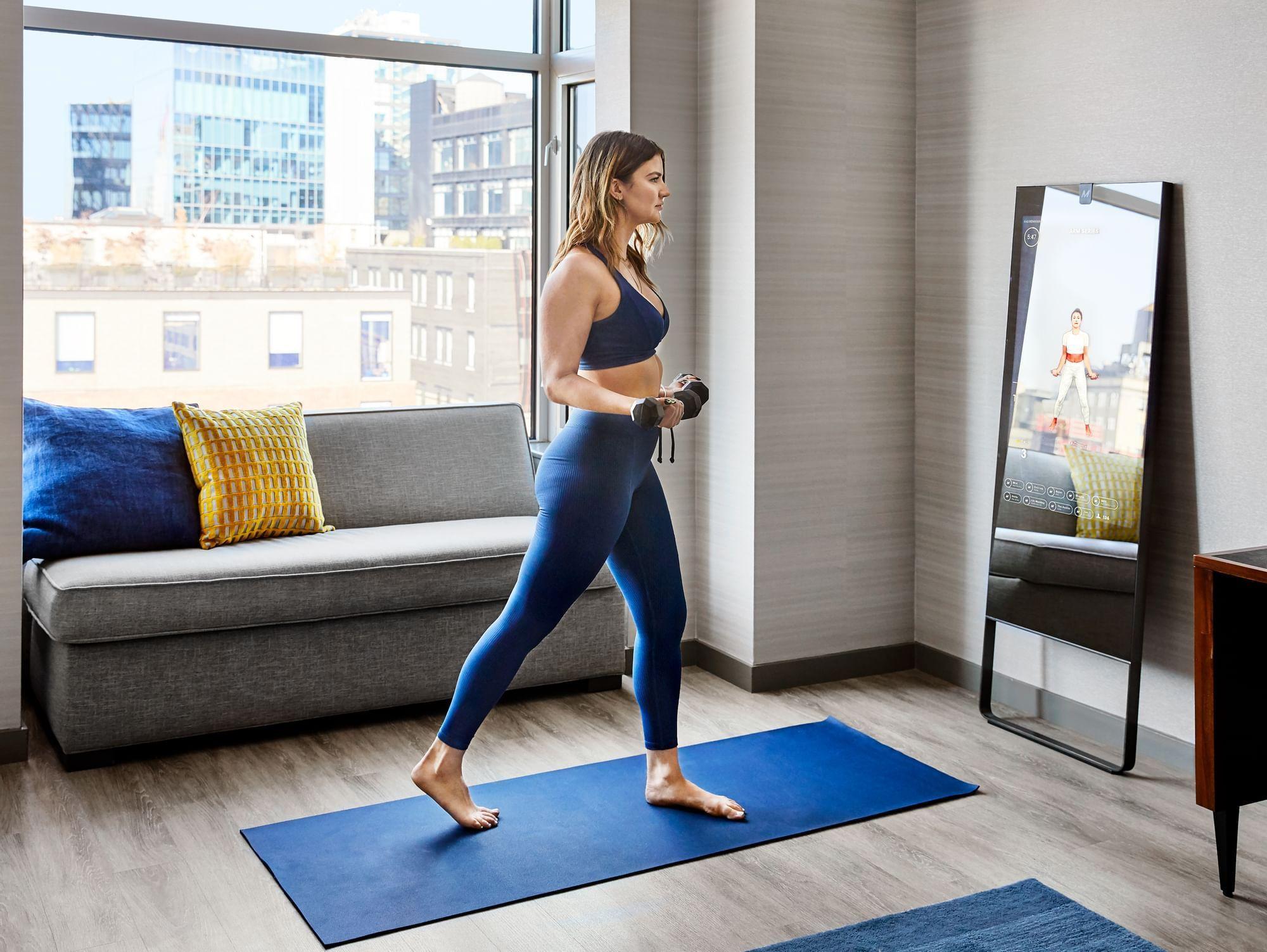 a woman exercising using a smart mirror