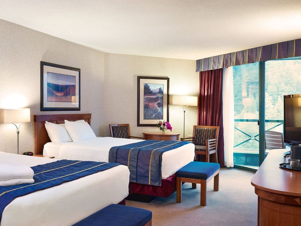 two beds in hotel room with balcony
