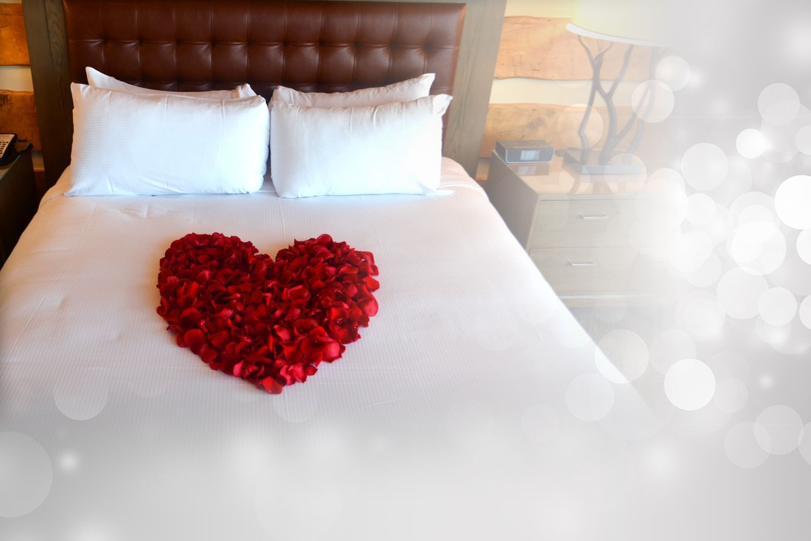 A queen size bed with a heart made of roses on it
