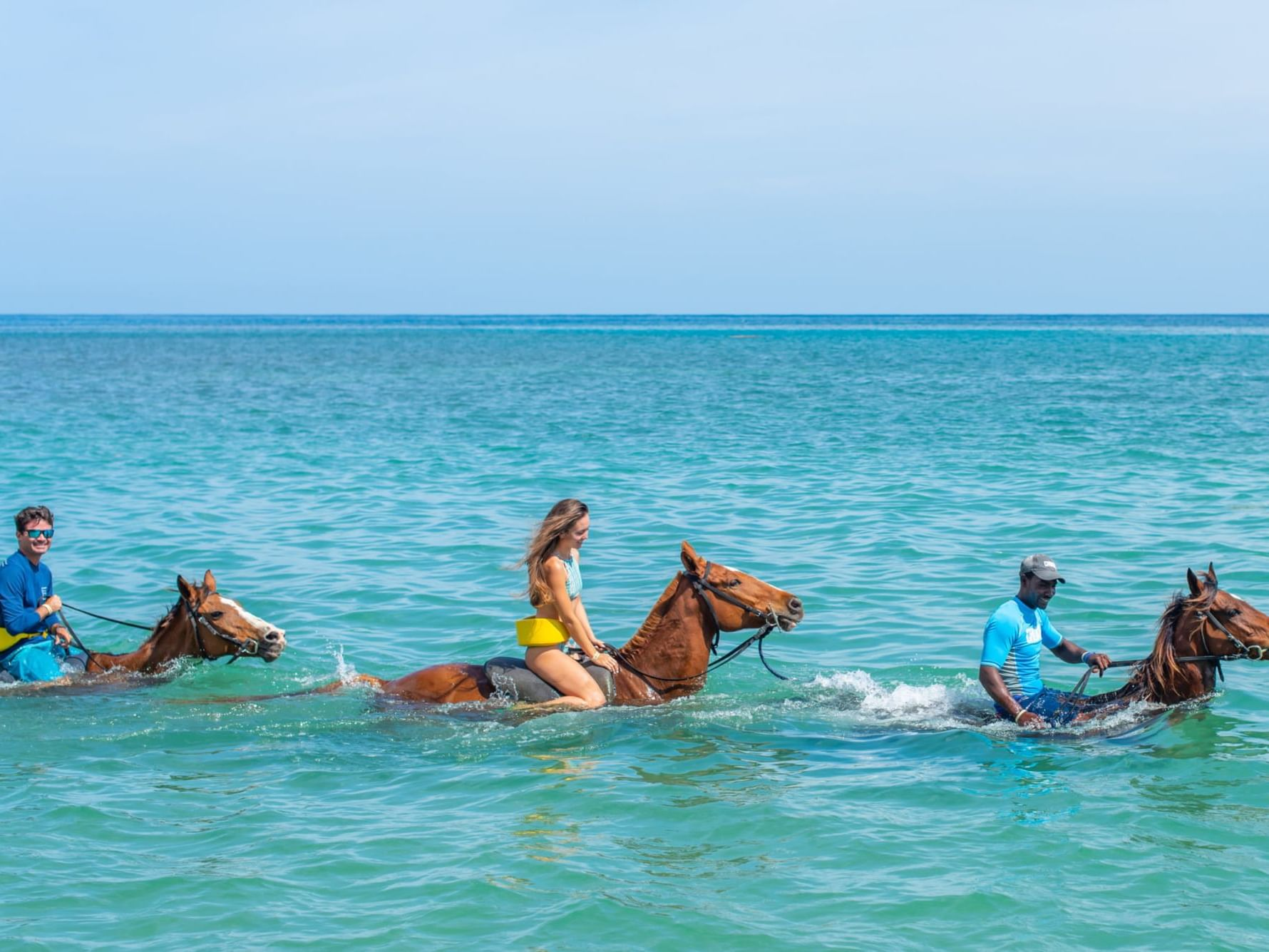 Three people on a horseback ride in the beach at Round Hill Hotel & Villas