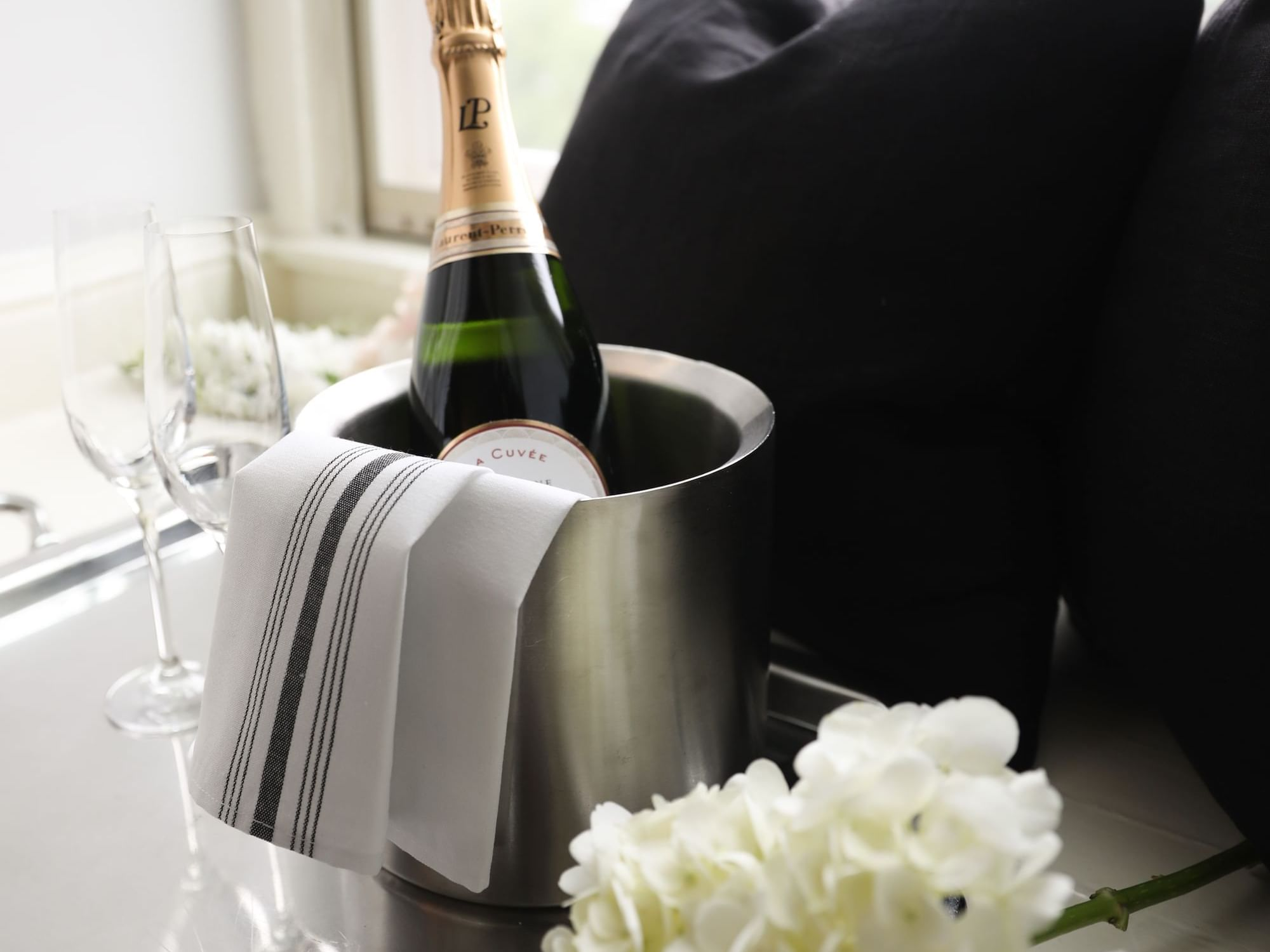 A bottle of champagne in an ice bucket with two glasses and flowers.