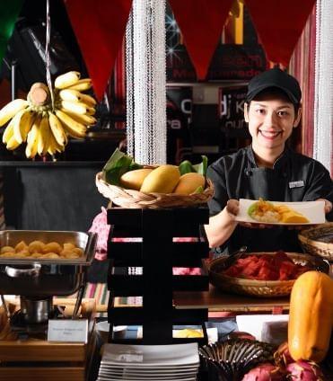A girl serves food at a restaurant in Dream Thailand Bangkok