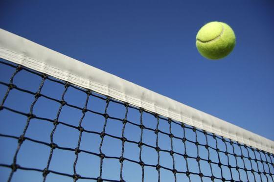 A tennis ball flying over a net