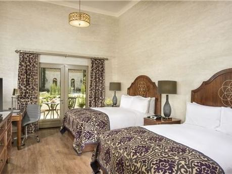 A room which includes Two queen size beds, a writing desk and  glass double doors leading out to the patio.