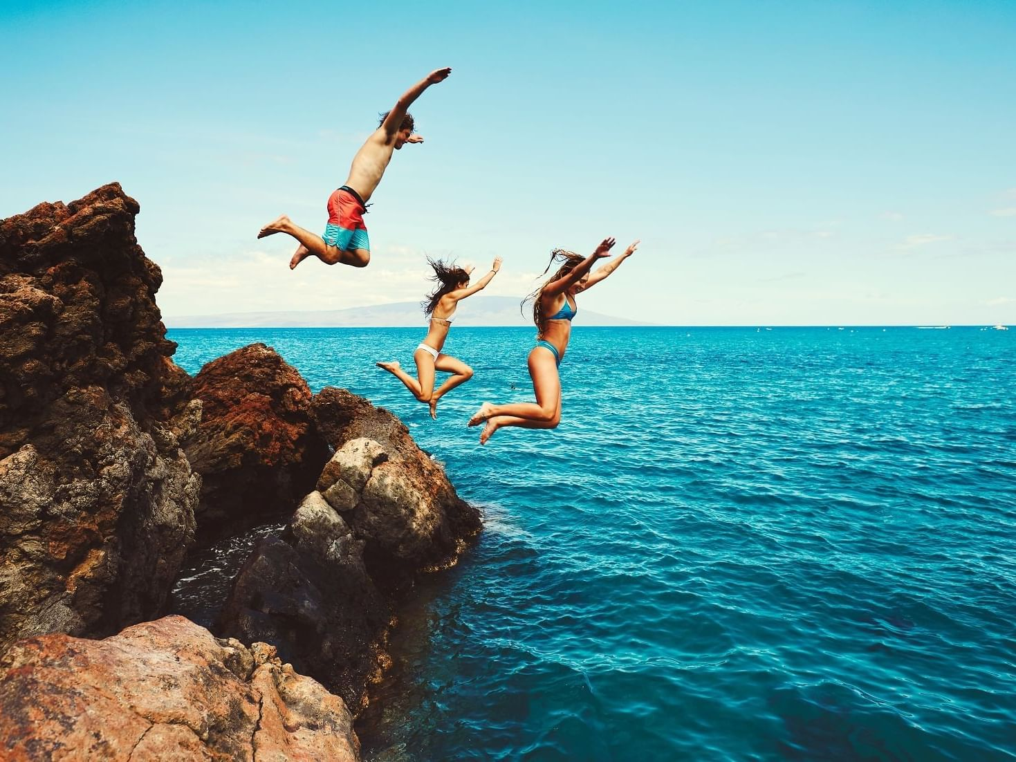 Three people jumping off the cliff at Daydream Island Resort