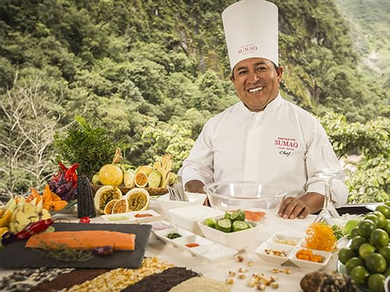 A chef posing for a picture with ingredients at Hotel Sumaq