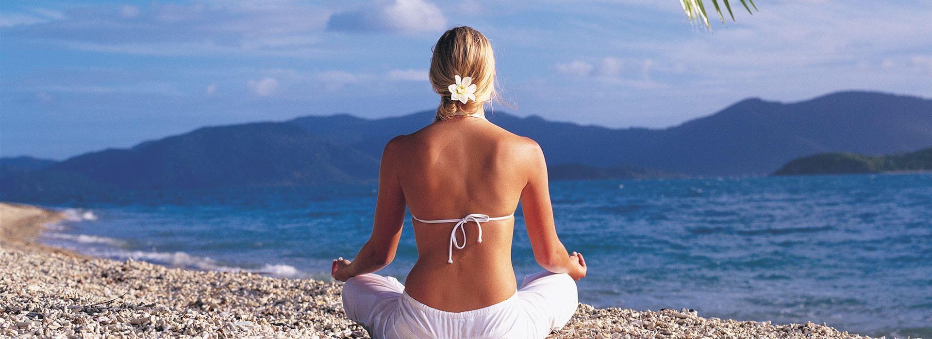 Woman practicing Yoga on beach at Daydream Island Resort