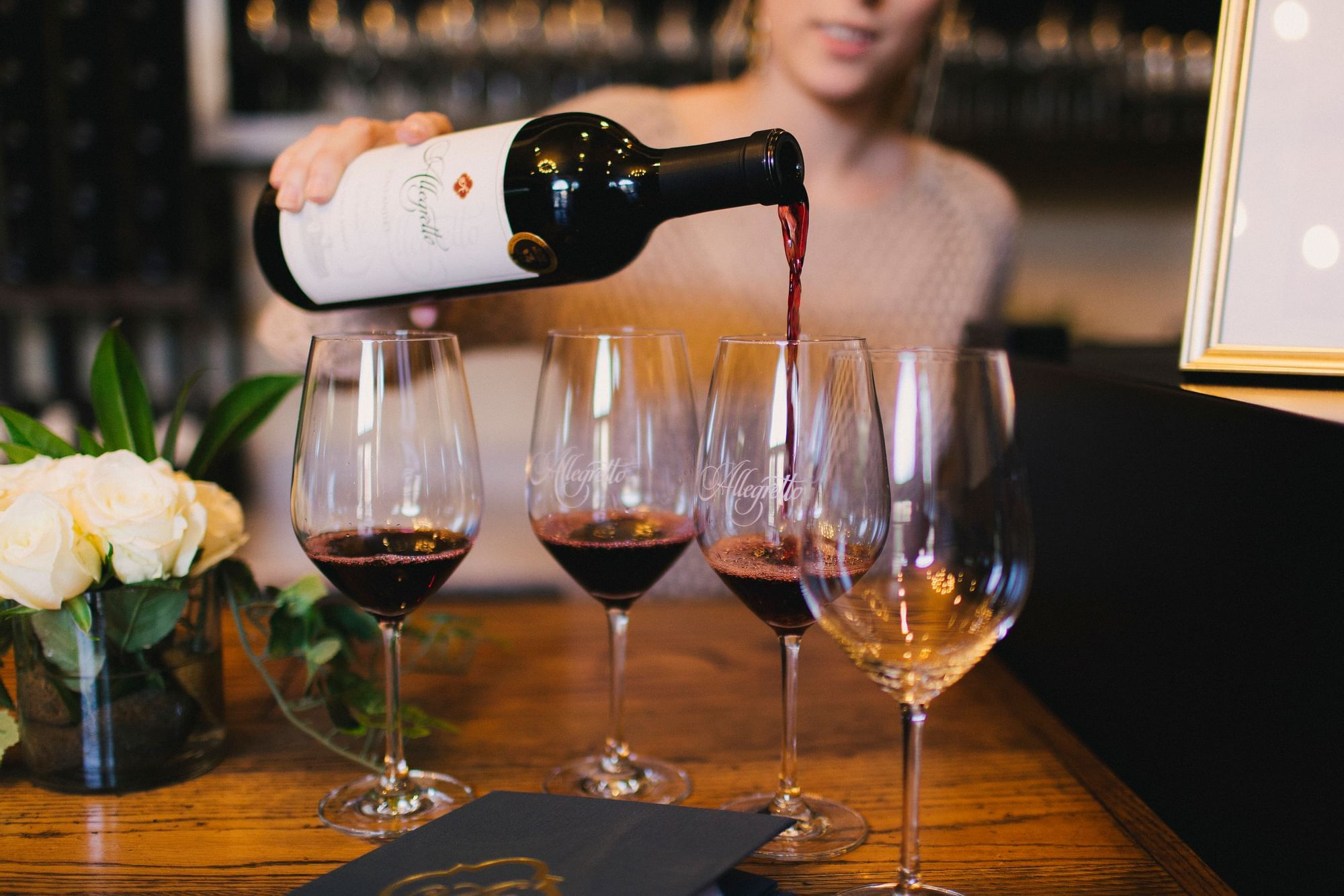 Four wine glasses lined up.  Woman pouring red wine.