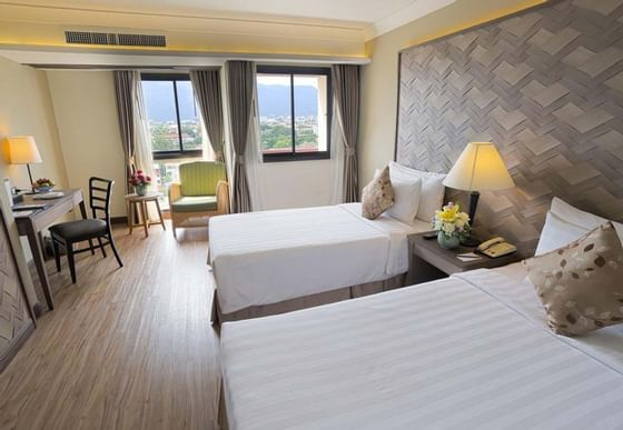 Room with two single beds and work desk at Amora Hotel