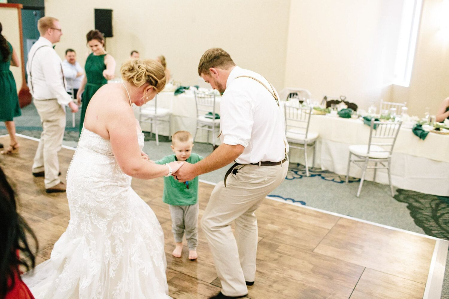 a bride and groom dance with a little kid