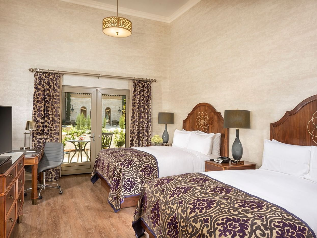 Hotel room with 2 queen beds, tv, and door to terrace