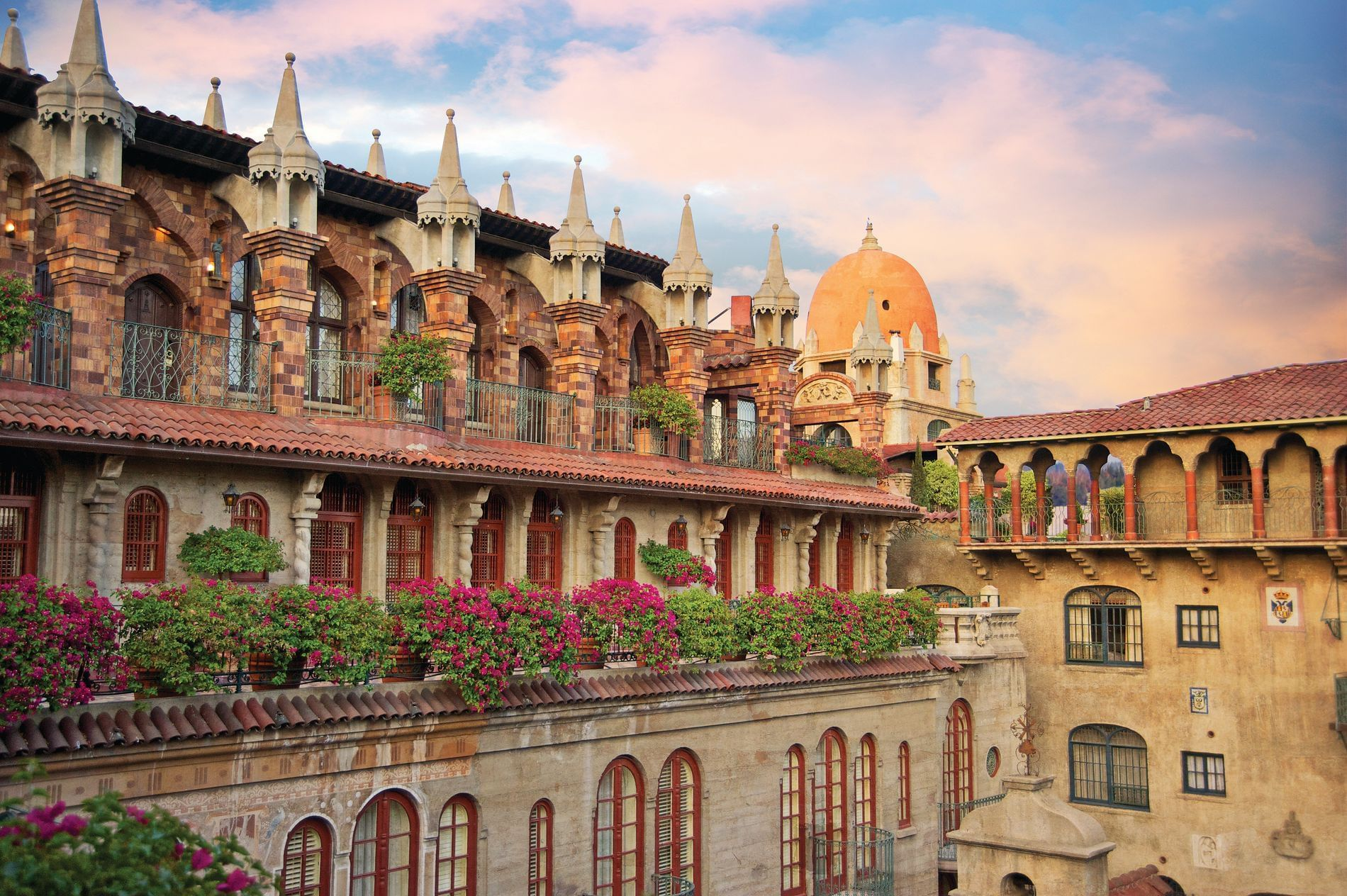 exterior of Mission Inn with balconies, windows and flowers