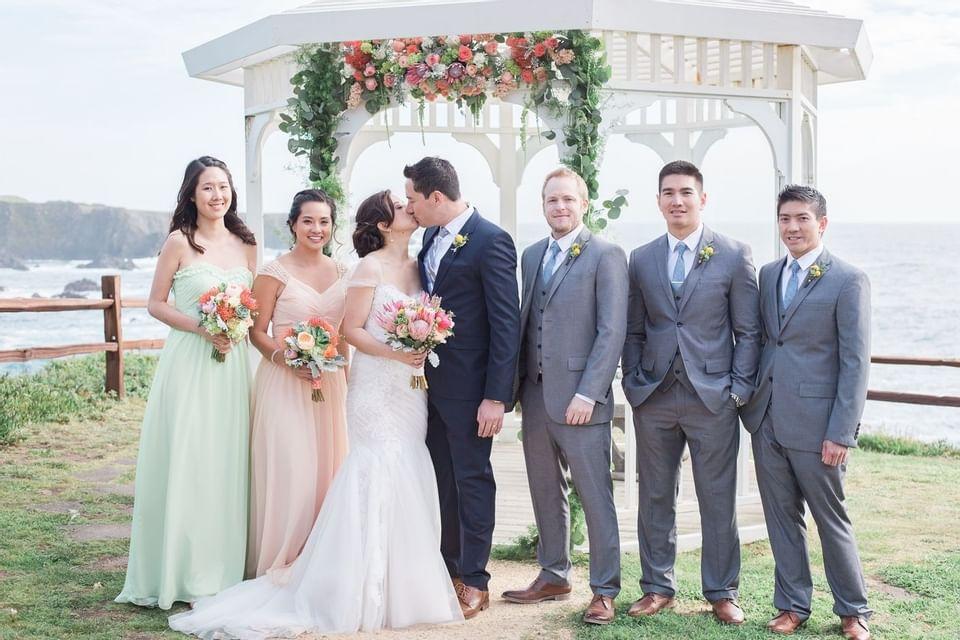 Newlyweds kissing near the coastline at Heritage House Resort