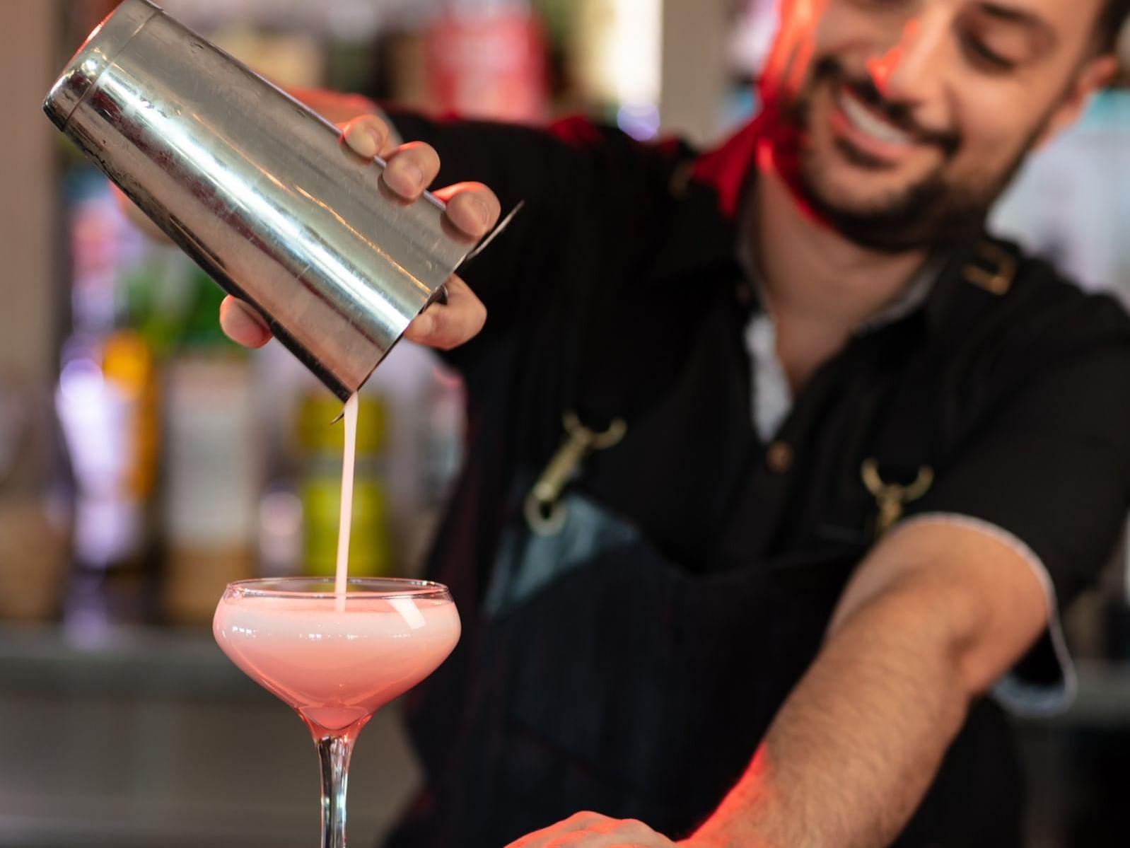 Bartender pouring pink cocktail
