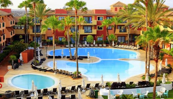 Pool With Palm Trees At Resort In Spain