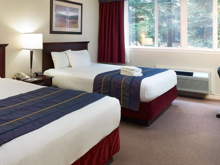two beds in hotel room with window