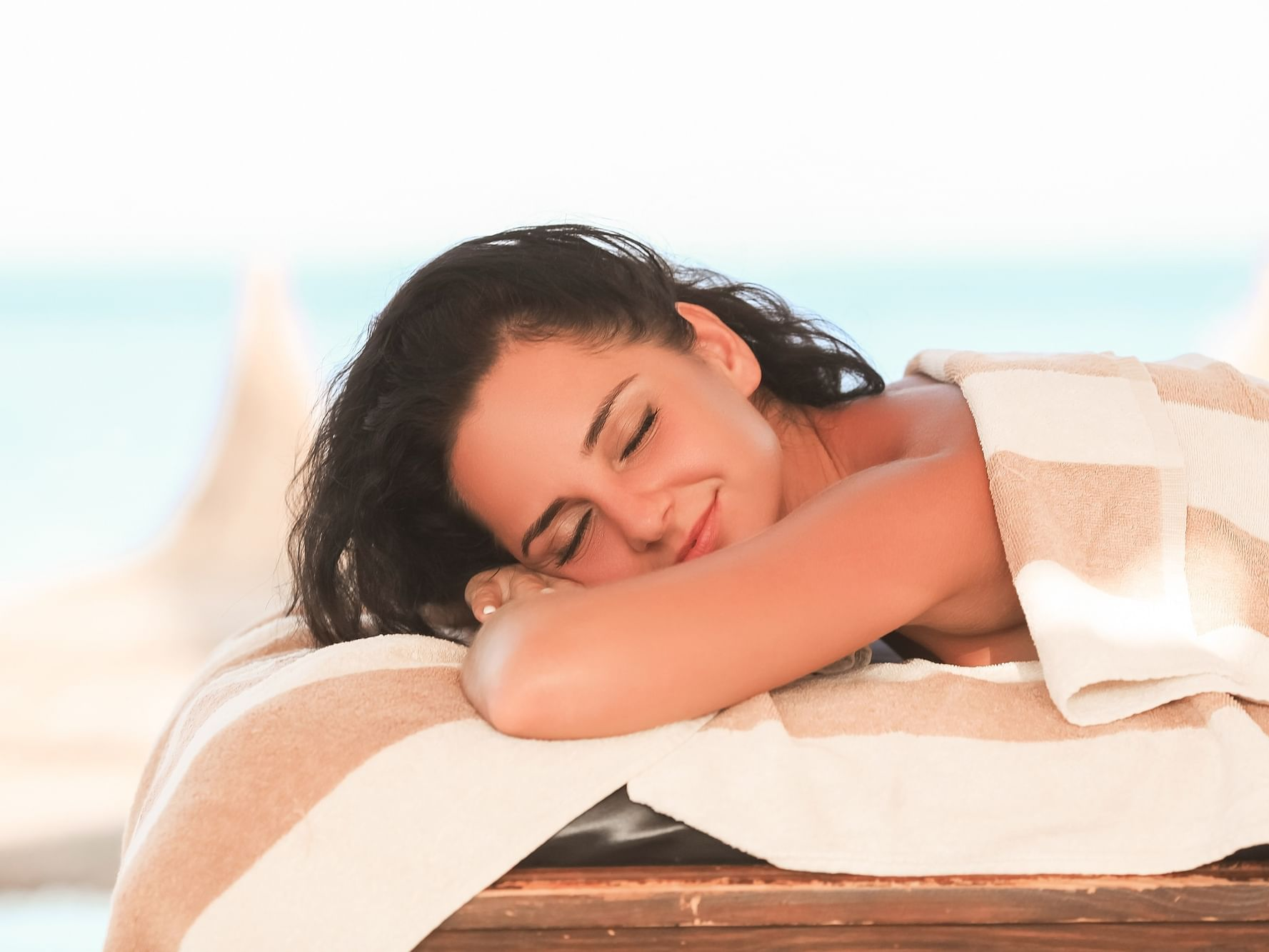 Woman relaxing on outdoor spa bed at Daydream Island Resort
