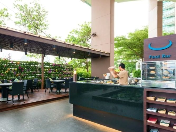 A man preparing cocktails in the Pool Bar at Chatrium Hotel Riverside Bangkok