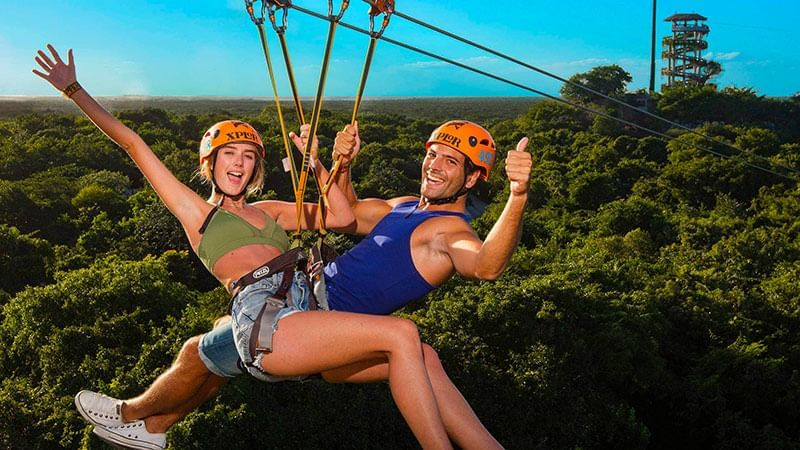 A couple ziplining at The Reef Resorts