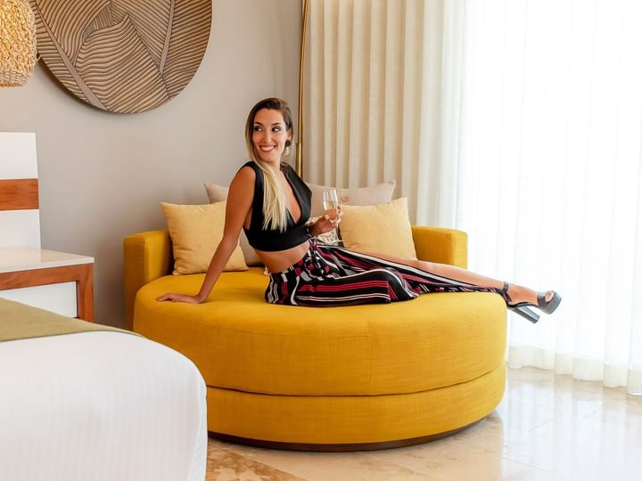A woman lying on a yellow sofa in a room at The Reef 28