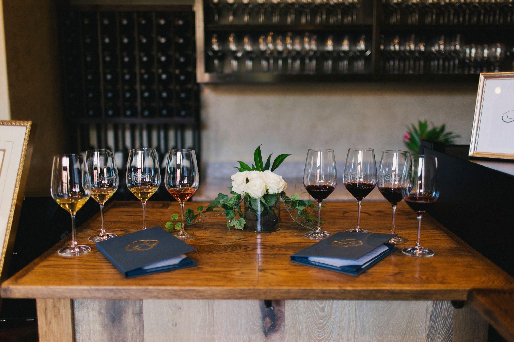 Eight glasses of wine split by a white flower arrangement