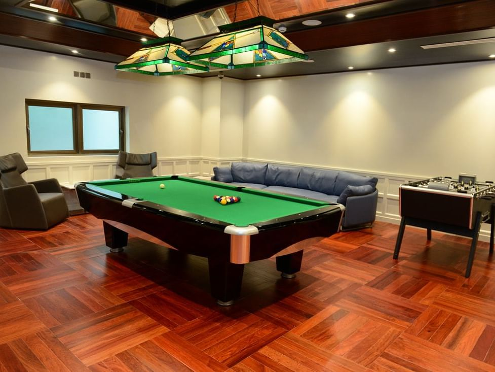 room with pool table, soccer table and lounge chairs