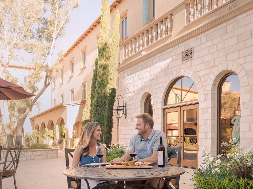 A woman and mad sitting at table outside of Allegretto Vineyard Resort