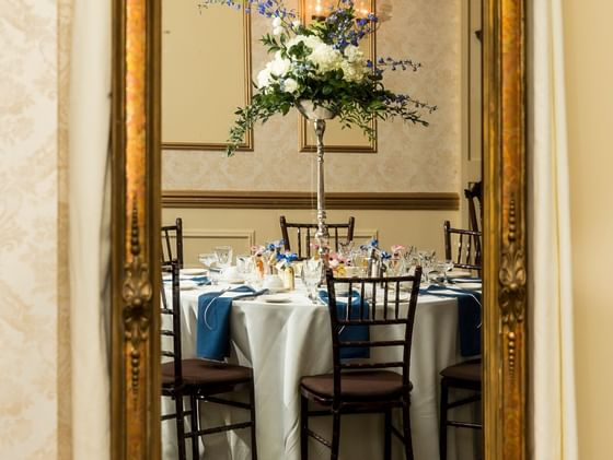 mirror reflecting ballroom table and chaird with centerpiece