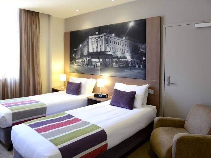 Superior room with 2 Single Beds and a chair at Grosvenor Hotel
