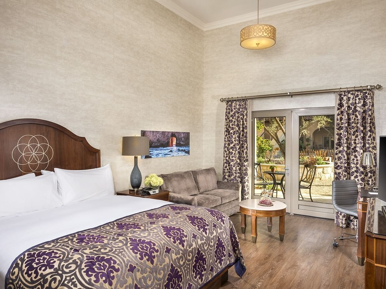A room which includes a king size bed, sofa and coffee table, a writing desk and glass double doors leading out to the patio.