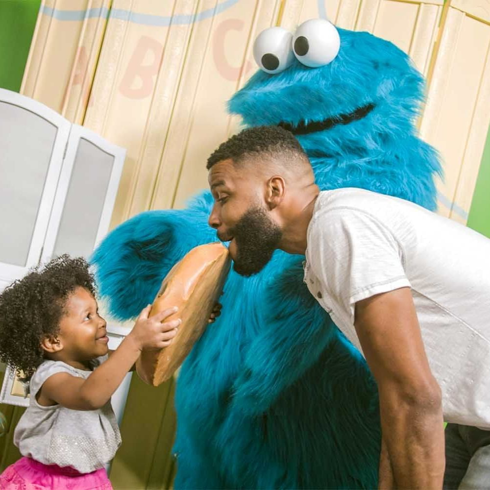 a little girl and her dad with a Sesame Street character