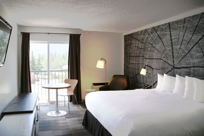 Bed in hotel room with balcony and artwork of a tree trunk