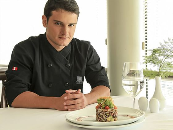 A chef presenting a nicely plated food at Hotel Sumaq
